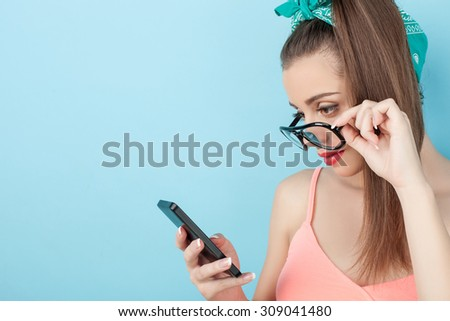 Pretty hipster girl is holding a mobile phone. She is messaging to her friend. The girl is looking at the technology seriously and touching her eyeglasses. Isolated and copy space in left side - stock photo