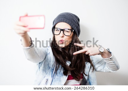 Pretty hipster girl taking selfie and making duck face. Sending kisses and holding peace sign. Instagram   - stock photo