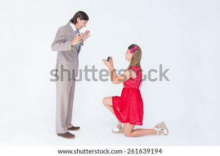 Pretty hipster on bended knee doing a marriage proposal to her boyfriend on white background - stock photo