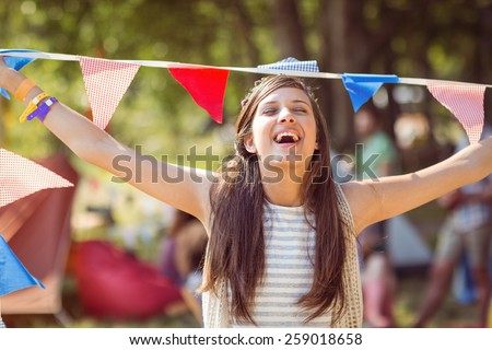 Pretty hipster posing for camera with flags at a music festival - stock photo