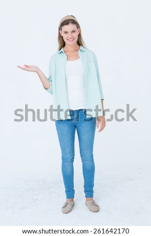 Pretty hipster presenting her hand on white background - stock photo