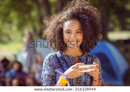 Pretty hipster sending text message at a music festival - stock photo