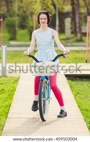Pretty hipster woman on bike in the park smiling and having fun outdoor - stock photo