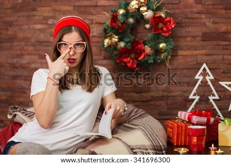 Pretty hipster woman reading a book at her home decorated for Christmas - stock photo