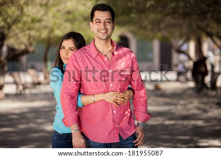 Pretty Hispanic brunette embracing her boyfriend and spending time with him outdoors