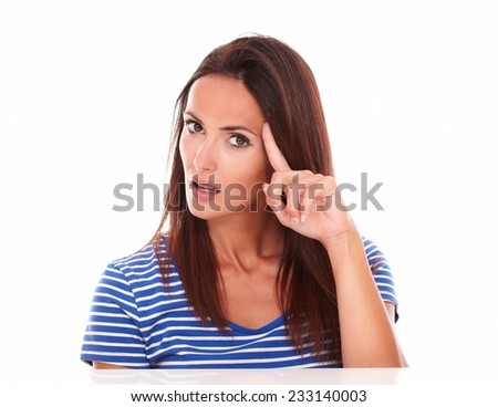 Pretty hispanic female wondering about a question while pointing to her forehead in white background