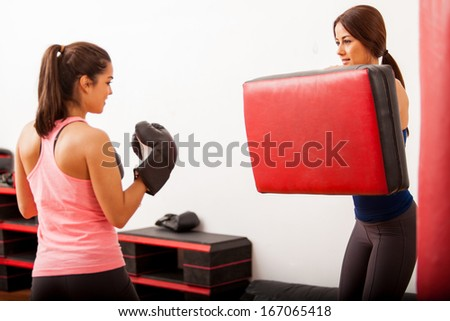 Pretty Hispanic friends training box together at a gym