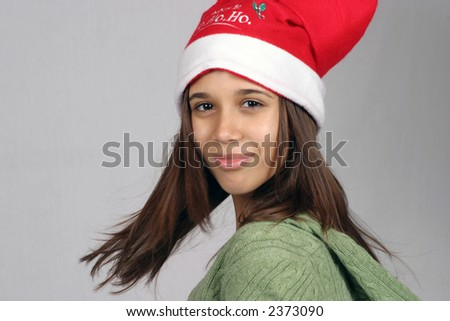 pretty hispanic girl smiling and twirling in santa hat - stock photo
