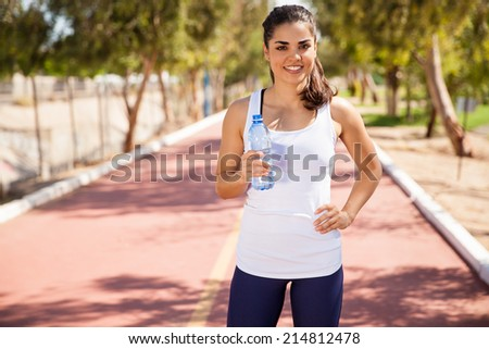 Pretty Hispanic girl taking a break and drinking some water after a long run - stock photo