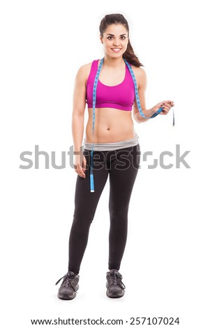 Pretty Hispanic personal trainer and diet coach holding a measuring tape and smiling - stock photo