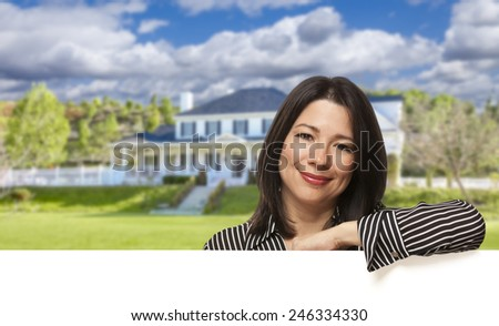 Pretty Hispanic Woman Leaning on White in Front of Beautiful House. - stock photo