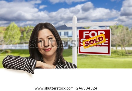 Pretty Hispanic Woman Leaning on White in Front of Beautiful House and Sold For Sale Real Estate Sign. - stock photo