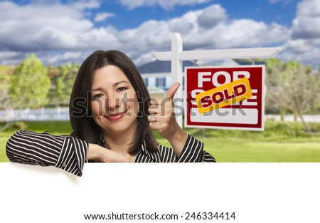 Pretty Hispanic Woman Leaning on White with Thumbs Up in Front of Beautiful House and Sold For Sale Real Estate Sign.