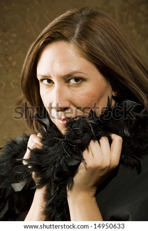 Pretty Hispanic Woman Wearing a Feather Boa in front of Gold Wallpaper - stock photo