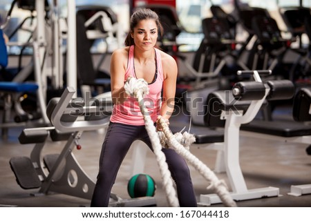 Pretty Hispanic young woman doing some crossfit exercises with a rope at a gym - stock photo