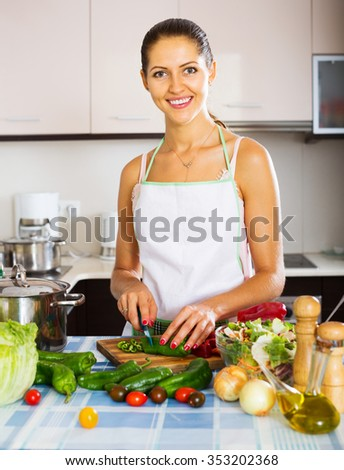 Pretty housewife standing at kitchen table with different vegetables