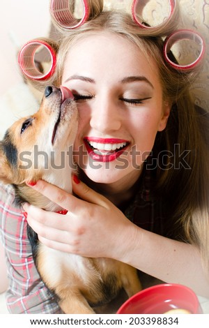pretty hug: closeup portrait on gorgeous beautiful blond young woman with great dental teeth whitening care, eyes closed and curlers on her head having fun hugging with little dog in her arms - stock photo