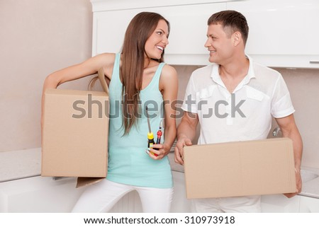 Pretty husband and wife are packing their staff for moving in another house. They are carrying cardboard boxes and smiling. The woman is holding screwdriver and pliers. She is looking at man with joy  - stock photo
