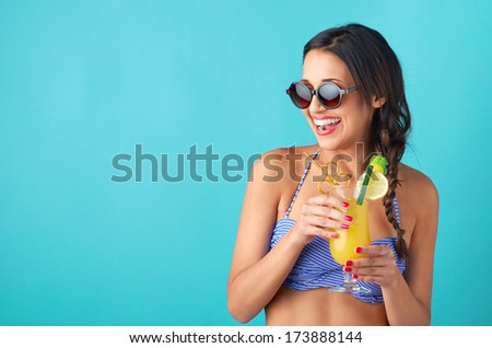 Pretty indian girl holding cocktail wearing a bikini, with red lips and nails isolated on bright blue background - stock photo