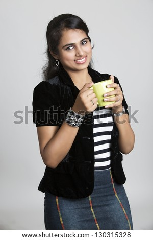 Pretty Indian girl posing with tea cup in studio background. - stock photo