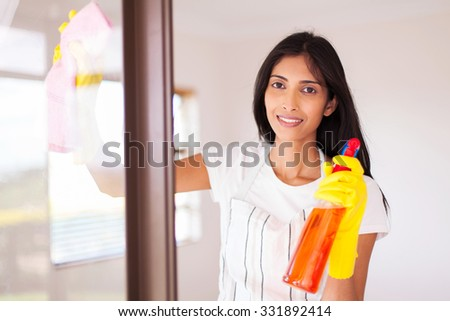 pretty indian housewife cleaning window glass - stock photo