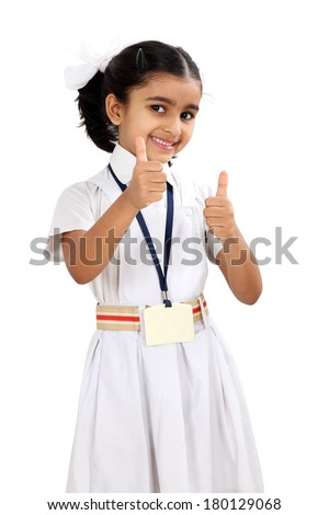 Pretty Indian little school girl showing thumbs up against white background - stock photo