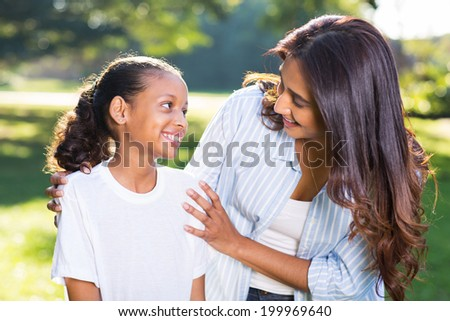 pretty indian mother talking to her beautiful daughter outdoors - stock photo