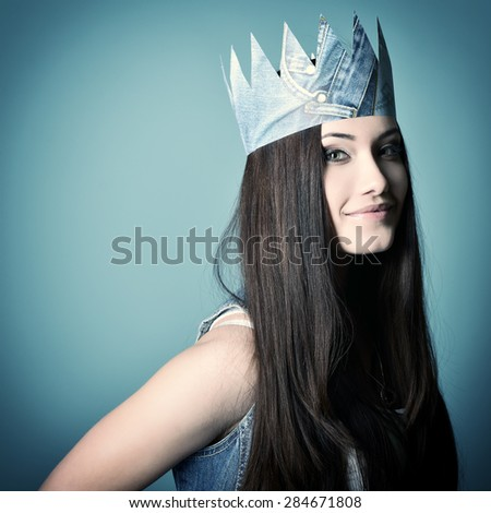 Pretty jeans princess. Beautiful girl in jeans and paper crown over blue background. Image toned - stock photo