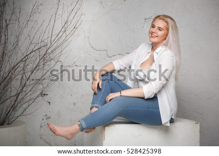 Pretty joyful blonde woman sits on a large size gray background in full length.