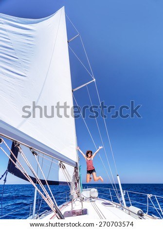 Pretty joyful woman in bright sunny day having fun on sailboat, jumping on the deck of luxury water transport, active summer vacation - stock photo
