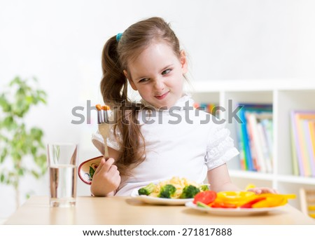 pretty kid girl looking loathingly at healthy vegetables - stock photo