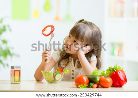 pretty kid girl refusing to eat her dinner healthy vegetables - stock photo