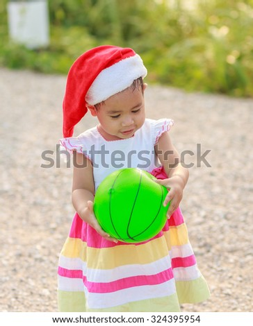 Pretty kid holding green ball and playing smiling at the park - stock photo