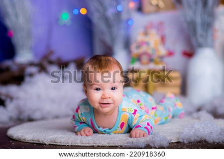 pretty kid on the flour in a New Year's suit near a Christmas tree. blue accent decor - stock photo