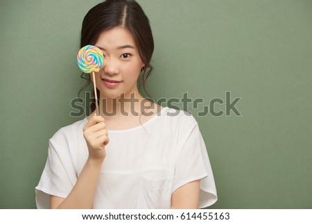 Pretty korean girl covering her eye stock photo royalty free pretty korean girl covering her eye with lollipop voltagebd Gallery