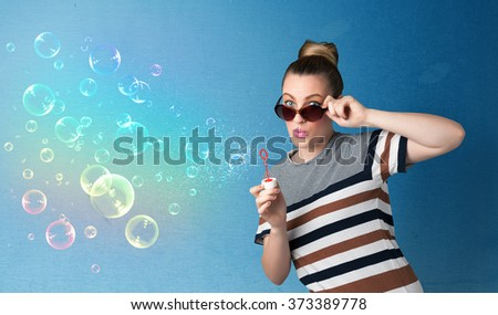 Pretty lady blowing big colorful bubbles on blue background - stock photo