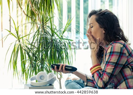 pretty lady bored watching TV while hold remote in hand - stock photo
