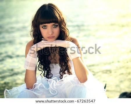Pretty lady in a wedding dress on sea - stock photo