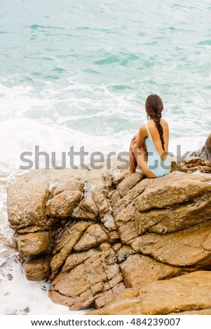 Pretty lady in full body swimsuit with long healthy hairs sit on big stone on the rock beach during sea ocean storm. Big waves near her legs. Concept of danger, sad, bad emotions.