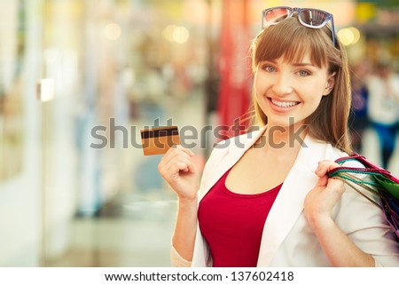 Pretty lady showing credit card in the mall - stock photo