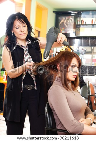 Pretty lady sitting while hairdresser dries her hair - stock photo