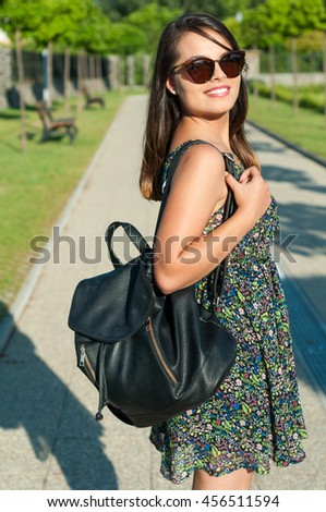 Pretty lady smiling wearing summer dress backpack and sunglasses outside in park