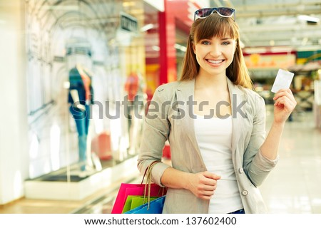 Pretty lady with shopping bags showing credit card