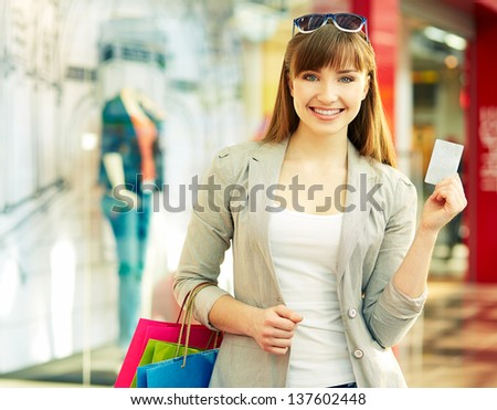 Pretty lady with shopping bags showing credit card - stock photo