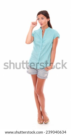 Pretty latin in shorts jeans standing full length and wondering about a question while looking to her right in white background - copyspace - stock photo