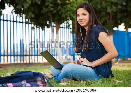 Pretty Latin teenage girl using a laptop and wearing earbuds while doing her homework outdoors