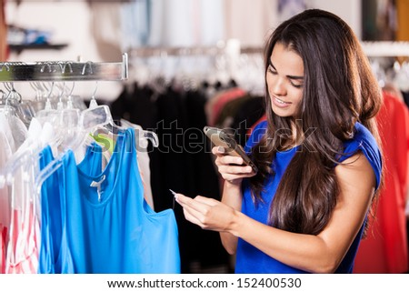 Pretty Latin woman taking a snapshot of a price tag in a clothing store - stock photo