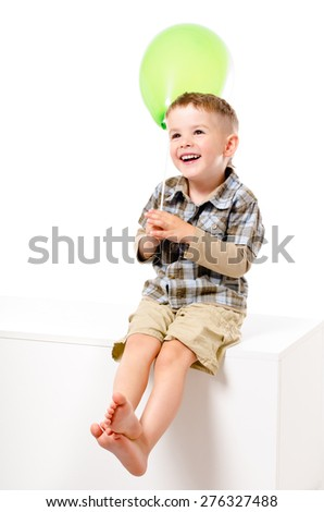 Pretty laughing boy with balloon sitting isolated on white background - stock photo