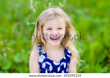 Pretty laughing little girl with long blond curly hair, outdoor portrait in summer park on bright sunny day. Smiling child in green grass field with purple flowers. Closeup portrait. - stock photo