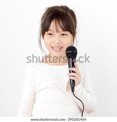 Pretty little asian girl with the microphone in her hand - stock photo